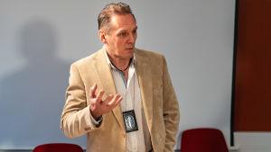 Polisen Hannu Kortelainen står civilklädd i ett mötesrum på polisstationen.