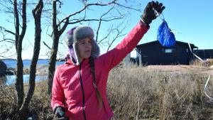 Kvinna i pälsmössa håller upp en trasig ballong.
