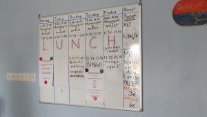 En whiteboardtavla med schema över program på olika veckodagar. Bland annat bingo, frågesport, morgongröt och andakter plus lunch och mathjälp.