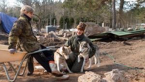 En man och en kvinna pausar från byggarbete, mannen lutar mot en skottkärra och kvinnan gullar med två huskyhundar.