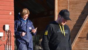 Veterinär Johanna Korpela och pälsfarmare Tobias Andersson på väg ut ur ett skugghus.