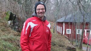 Hans Ginlund i röd rock framför ett gammalt rött trähus i Dalsbruk med gråa träd i bakgrunden.