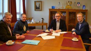 Fyra män runt ett bord.