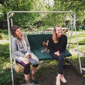 Kaksi naista istuu pihakeinussa vihreällä pihalla Paraisten Vanhalla Malmilla.