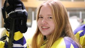 Laura Prinsén, hockeyspelare i Närpes Kraft C-juniorer, står i ishallen med gul spelskjorta