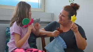 en flicka sitter på soffan med fingerdockor och håller på med talterapi med en talterapeut.