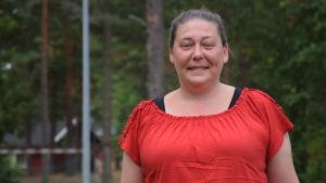 En bild på en kvinna i röd t-skjorta. hon heter Katrin Janser och ler på bilden. I bakgrunden syns tallskog.