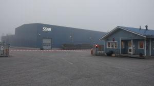 En fabrik i dimmigt septemberväder. Framför byggnaden en röd-vit bom  och ett rött trafikljus.