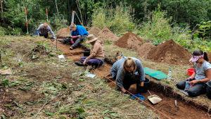 Personer sitter i ett sanddike på en arkeologisk utgrävning.