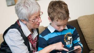 Äldre kvinna och en pojke i lågstadieåldern läser tillsammans.