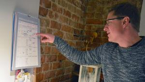 En man tittar i almanackan som hänger på väggen.