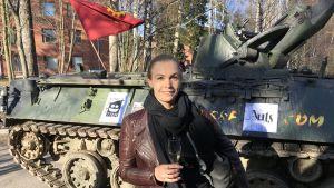 Kurator Vendla Sandström med ett skumvinsglas framför en pansarvagn.