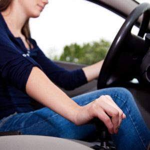 en ung kvinna kör bil. Man ser bara händer som håller om ratt och växelspak