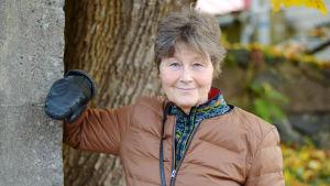 Karin Munsterhjelm står med ytterkläderna ute och lutar armen mot en betongstolpe. Hon ser in i kameran.