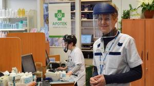 Monica Strandvall tar emot på Ingå apotek utrustad med ansiktsskydd av plexiglas.