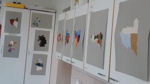 klassrumsvägg med världsdelar i olika färger klistrade på vitt papper