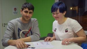 Shuaib från Afghanistan och Lilli från Finland lär sig första hjälpen på Walkers café i Sjundeå.