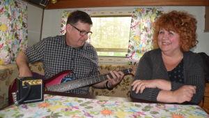 Man spelar elbas i en husvagn, frun sitter bredvid vid bordet.