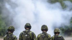 Soldater i stridsmundering står framför rök. De svenska soldater deltar i ett slutprov 2014.