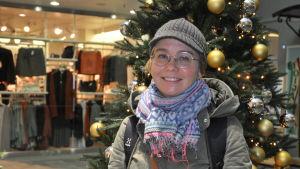 Sanna Sova står framför en julgran i köpcentret.