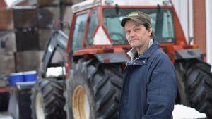 Man i keps står framför en traktor och ser in i kameran.
