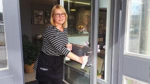 En kvinna står och håller upp en glasdörr in till en frisörsalong.
