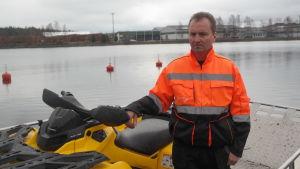 Thomas Grönroos står ombord på sin båt bredvid en fyrhjuling i Daösbruks hamn