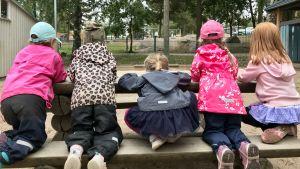 Fem barn ute på en bänk med ryggarna mot kameran.