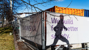 "Skanskan mainosteksti rakennustyömaalla: ""We build for a better society""."
