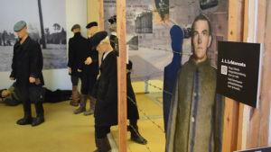 Utställningslokal med dockor i naturlig storlek föreställande fångar. På väggen fotografier av ett fångläger.