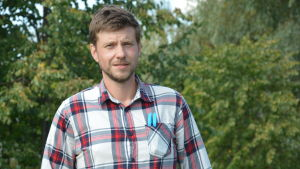 Porträtt av Jonas Bergström mot en somrig, grön bakgrund.