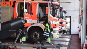En brandbil inne i garaget, branmanskläder hänger utanför.