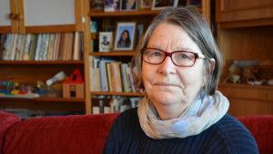 Vit kvinna med grå page och glasögon stter i en soffa.