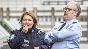 Rauni Kolehmainen (Kaarina Hazard) och Jarkko Larsson (Mikko Roihaä) står bredvid varandra i polisuniform.