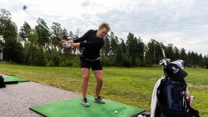 En kvinna står med klubban i luften, beredd att slå till en golfboll.