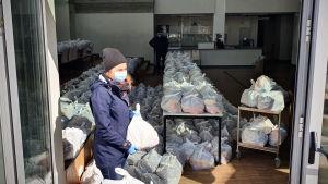 En kvinna delar ut lunchsäckspåsar som skolorna i Estland delar ut åt barnen en gång i veckan.