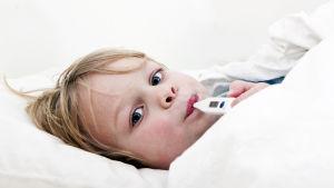Ett barn ligger till sängs med feberröda kinder och en febertermometer i munnen.