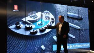 Oskar Levander står framför en stor skärm och pekar på en videoanimation.