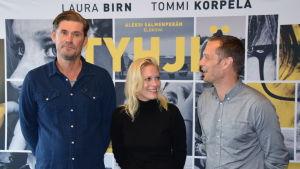 Skådespelarna Tommi Korpela och Laura Birn tillsammans med regissören Aleksi Salmenperä står framför filmplanschen till Tyhjiö.