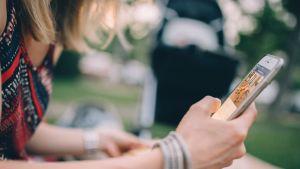 Kvinna surfar på sin mobiltelefon.