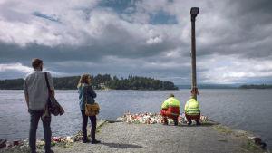 Harald (Marius Lien) och Anine (Alexandra Gjerpen) står vid bryggan mot Utöya, två ambulansmän ställer ner blommor..