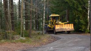 Ett gult fordon som jobbar med att jämna ut en grusväg.