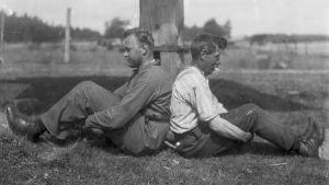 """Två män leker """"pina kalv"""", där man ska försöka skuffa den andra bakåt så att dennes knän böjs. Bilden är tagen 1930 i Finström, Åland."""