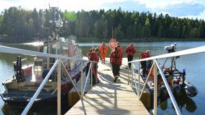 Flera män i röda overaller står på en brygga. Till vänster vid bryggan finns en större båt och på högra sidan av bryggan finns en gummibåt.