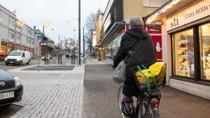 Kvinna cyklar på gatan, till höger affärslokal och till vänster motorhuven av en parkerad bil.