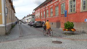 En cyklist med gul tröja cyklar på den stenlagda gatan mellan trähusen i Gamla Raumo.