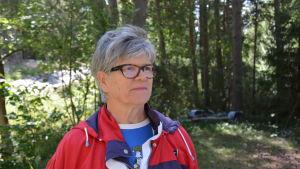 Närbild på Elisabet Nymalm. Hon står i skogsbrynet, har grått hår och glasögon.