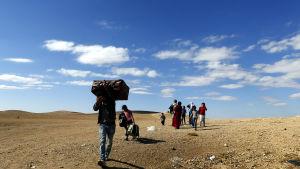 Folk på flykt undan IS överskrider gränsen mot Turkiet.