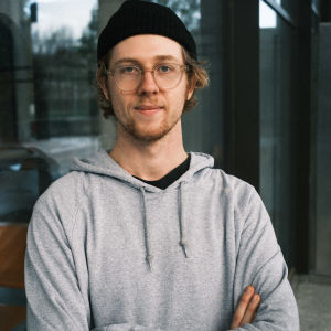 Porträttbild på Jonathan Terlinden, klädd i svart mössa och grå munkjacka.