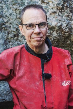 Keski-ikäinen mies, jolla silmälasit, pukeutuneena punaiseen haalaripukuun.